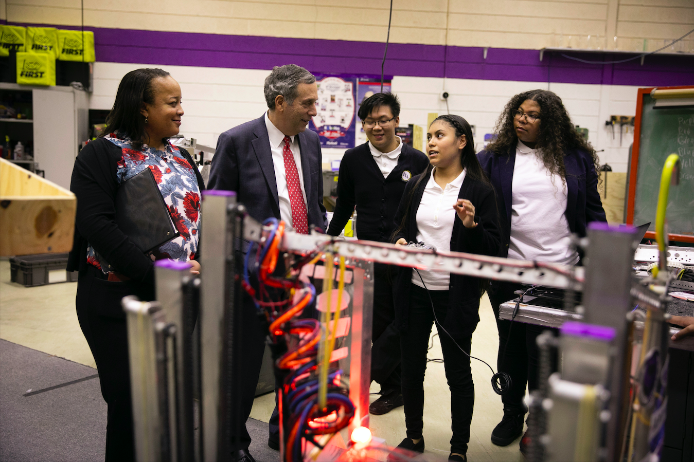 Students at International Technology Academy in Pontiac, Michigan give President Bacow and HGSE Dean Long a tour of the Robotics Lab.