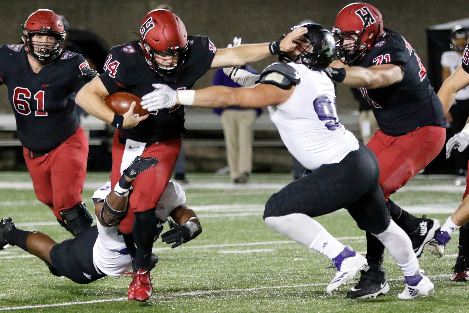 Quarterback Tom Stewart puts down a nice stiff-arm as he shakes off two tackles in Friday night's contest with Holy Cross.