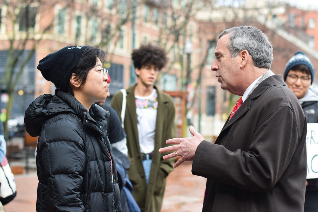 University President Lawrence S. Bacow speaks to Sally Chen '19 at a demonstration Friday where students and alumni called on Harvard to create an Ethnic Studies program.
