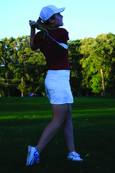 Sophomore Chloe Royston finishes a shot from the fairway.