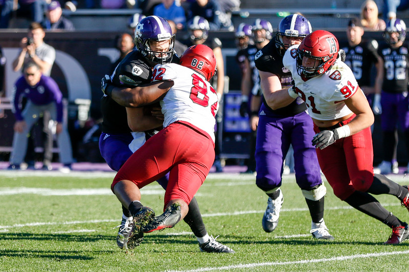 Sophomore defensive lineman Anthony Nelson wraps up the Holy Cross quarterback for one of five team sacks.