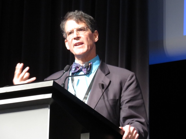 Dr. Eben Alexander is speaking at a podium.