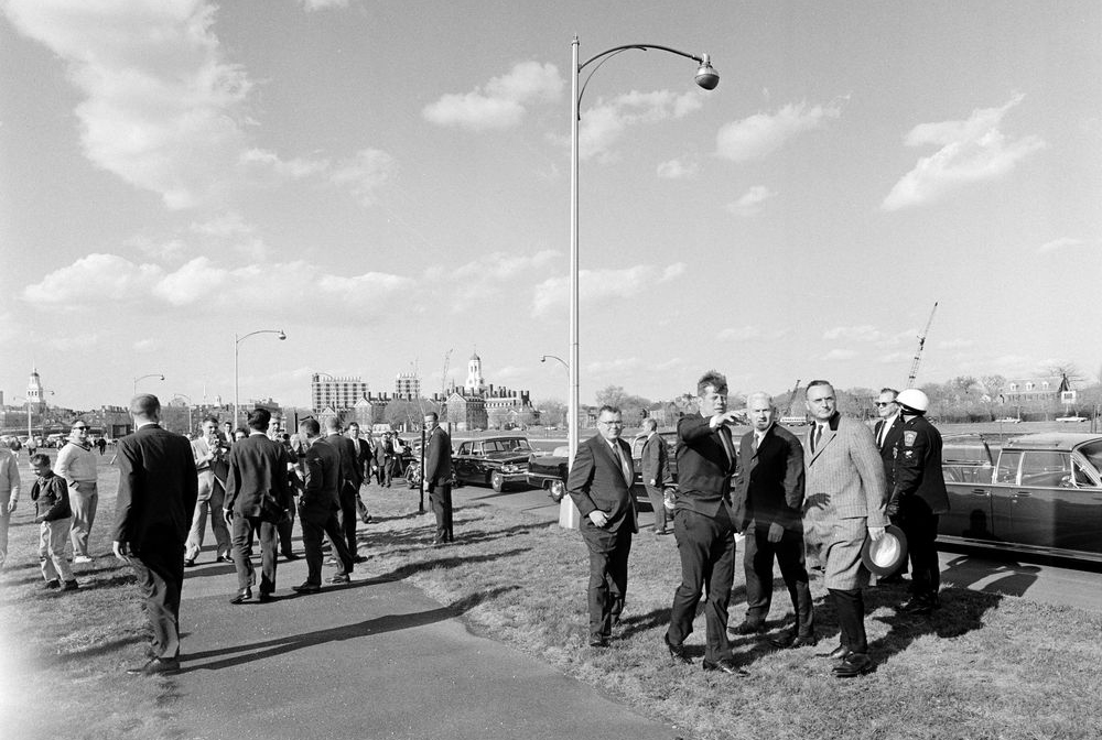 President John F. Kennedy '40 motions with his arm towards the proposed site of his future Presidential Library, along the banks of the Charles River in Boston, with Eliot House and Dunster House visible in the horizon.