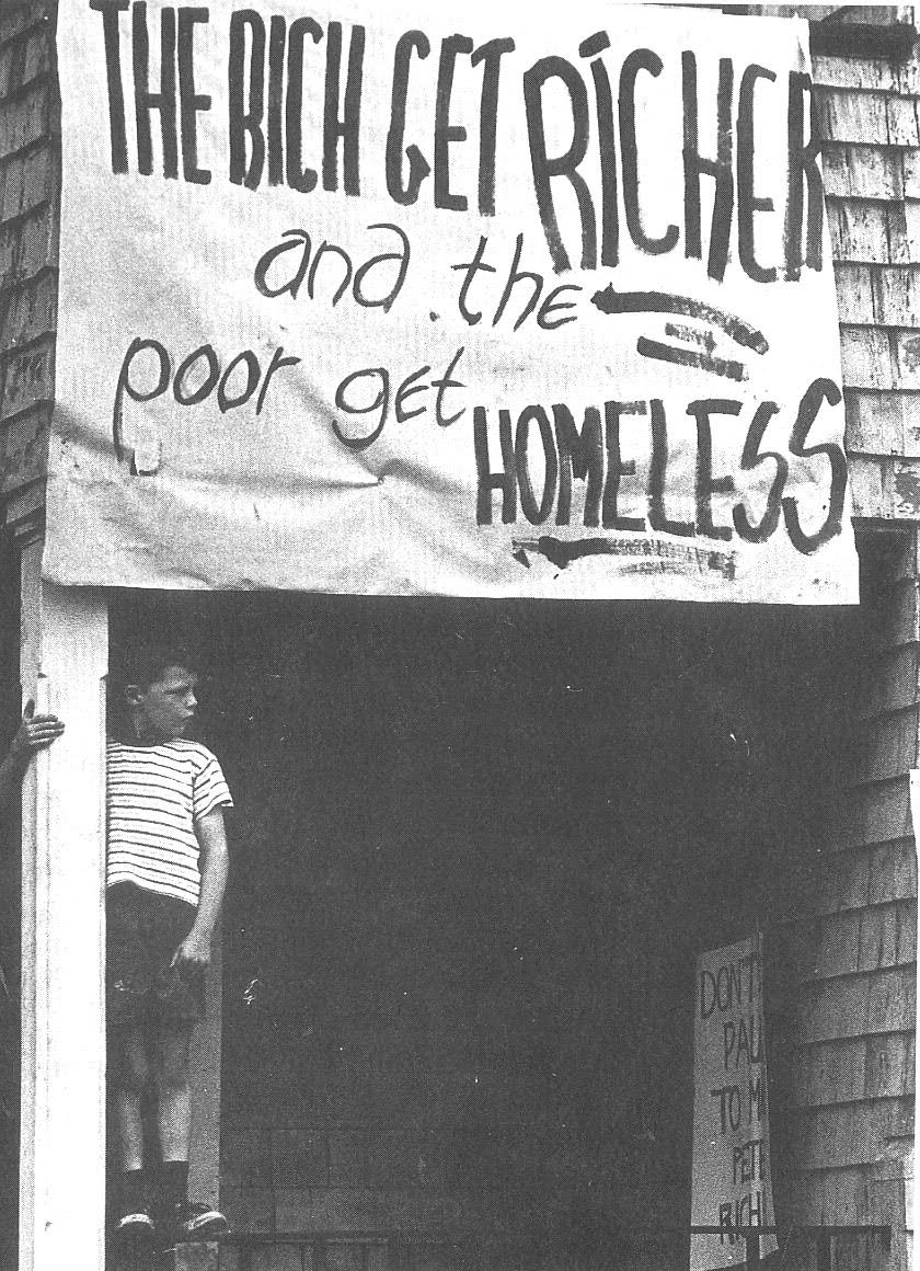 """A sign on a building in Barry's Corner in Lower Allston in the 1960s. It reads, """"The Rich Get Richer and the Poor Get Homeless."""""""