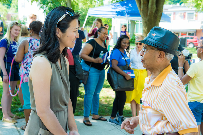 Wu talks to community members at a Roslindale ice cream social in 2019.