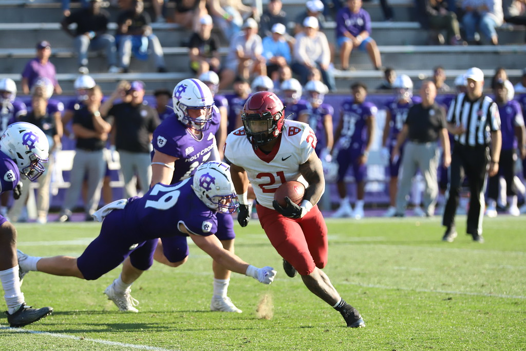 Sophomore running back Aidan Borguet leaves a pair of Holy Cross defenders in the dust. Borguet finished last Saturday's contest with 59 rushing yards and a touchdown.