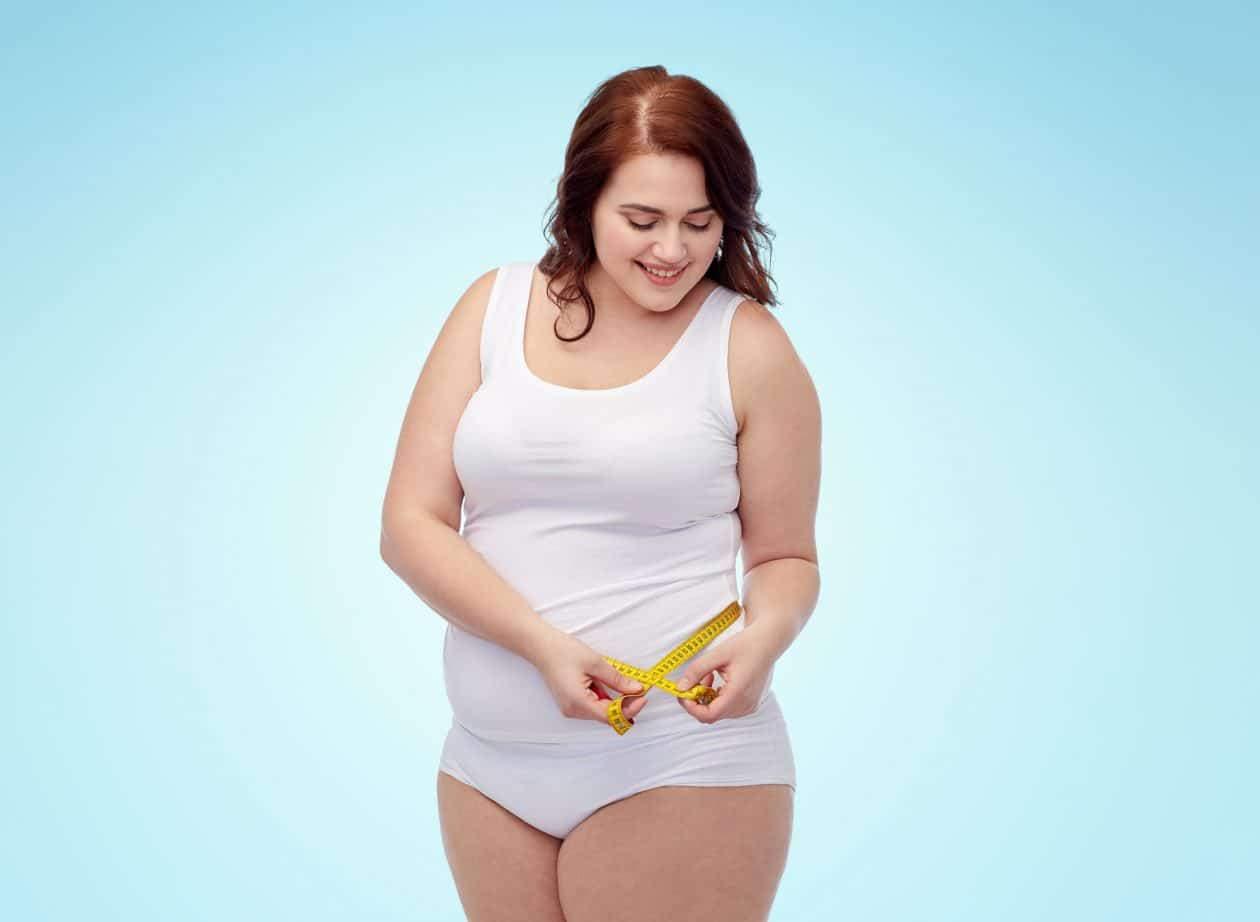 Plus size woman measuring herself