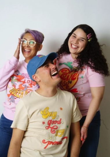 3 LGBTQIA+ people stand wearing various designs from gay pride apparel