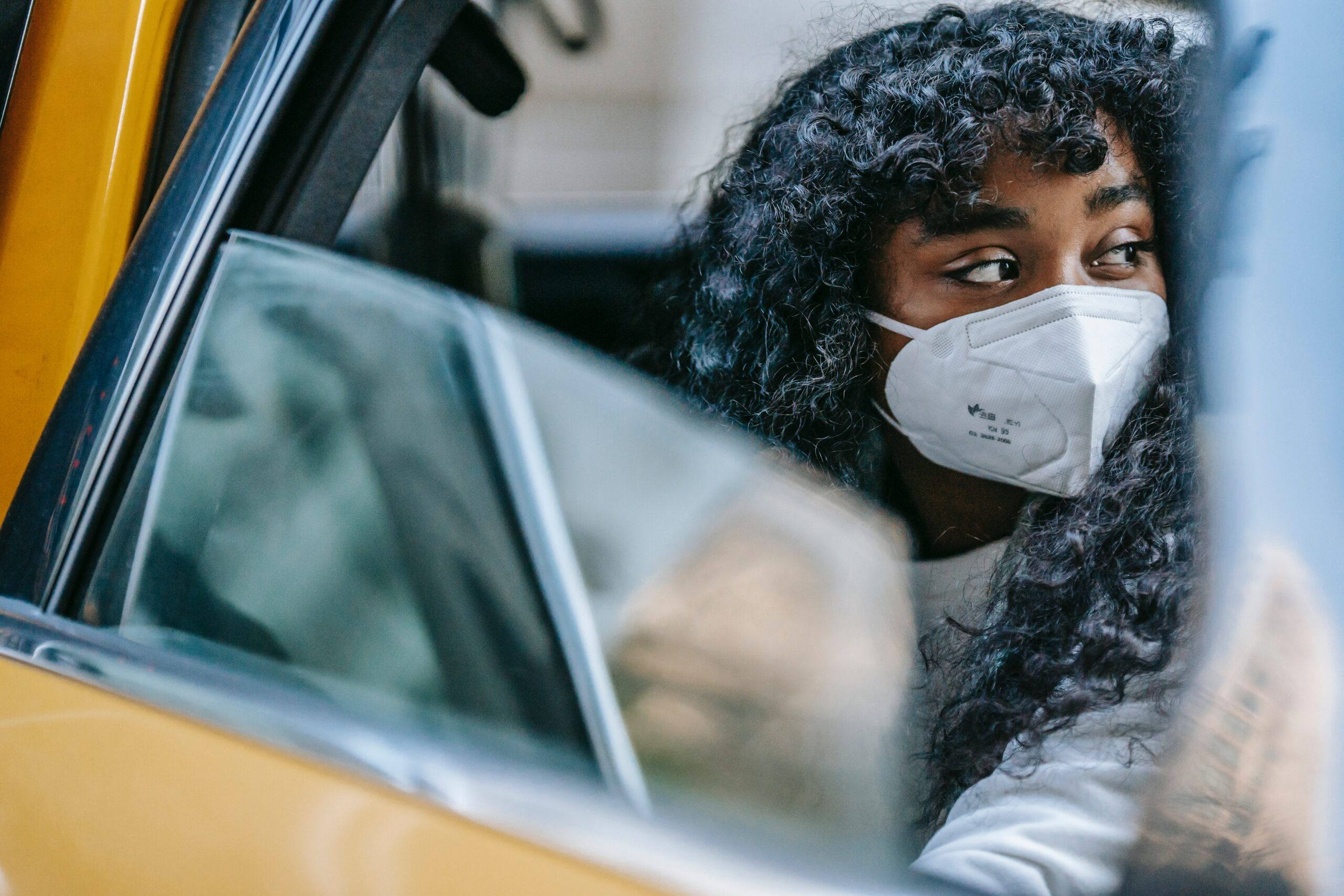 A Black person sits in a taxi wearing an N95 mask. Post Pandemic Plus Size Travel