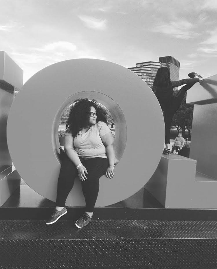 Ronnie, a Black perosn, sits in the O in a sign while traveling. The photo is in black and white, and they are wearing sneakers, black leggings and a short sleeve t shirt.
