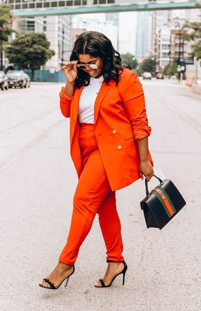 woman wearing a bright orange pantsuit with matching blazer posing in front of camera. with the street in the background.  12 Timeless Classics That Will Never Go Out of Style