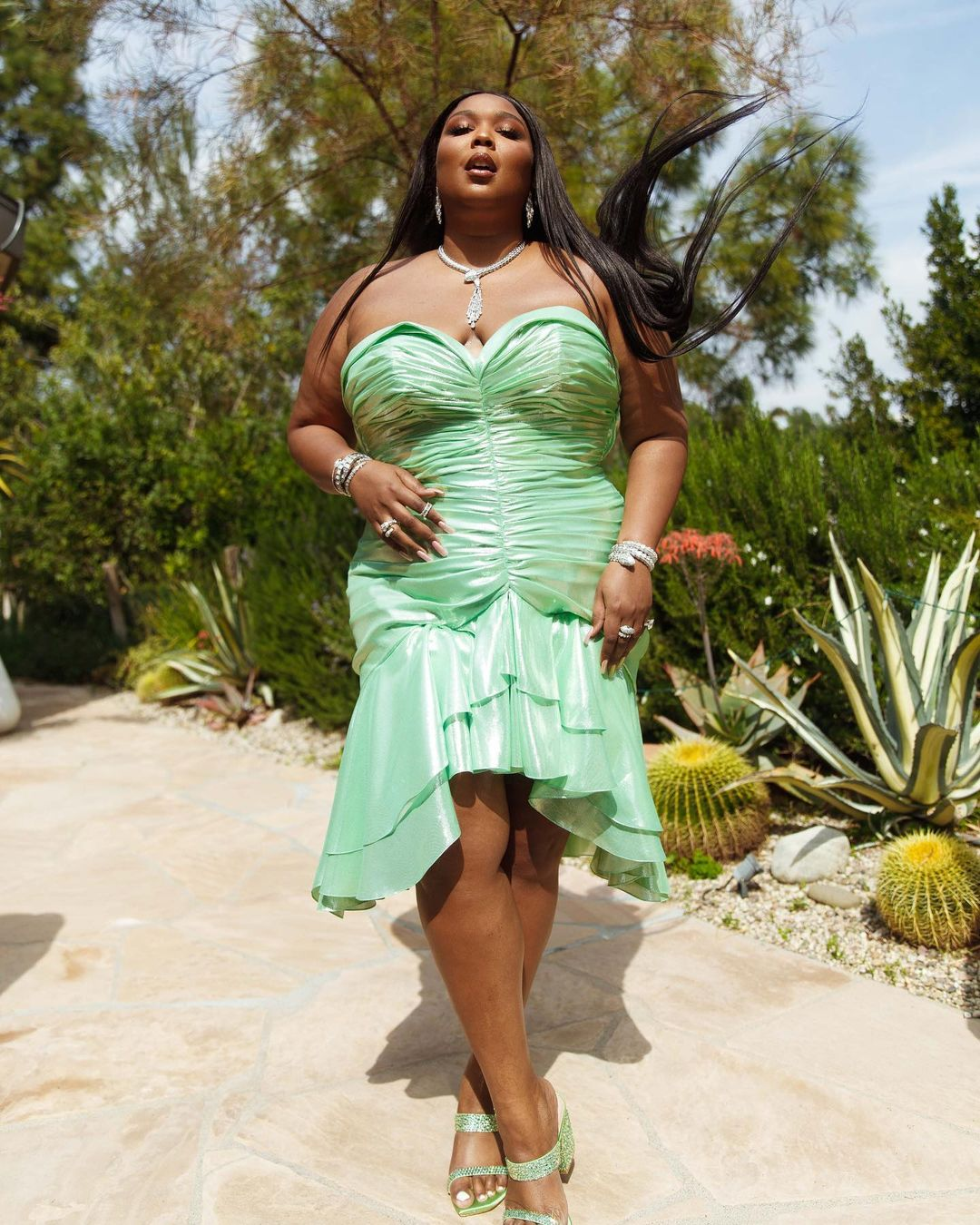 Singer Lizzo in a strapless green gown with ruching all throughout and a hi-low hemline. She is walking toward the camera. There is greenery in the background.