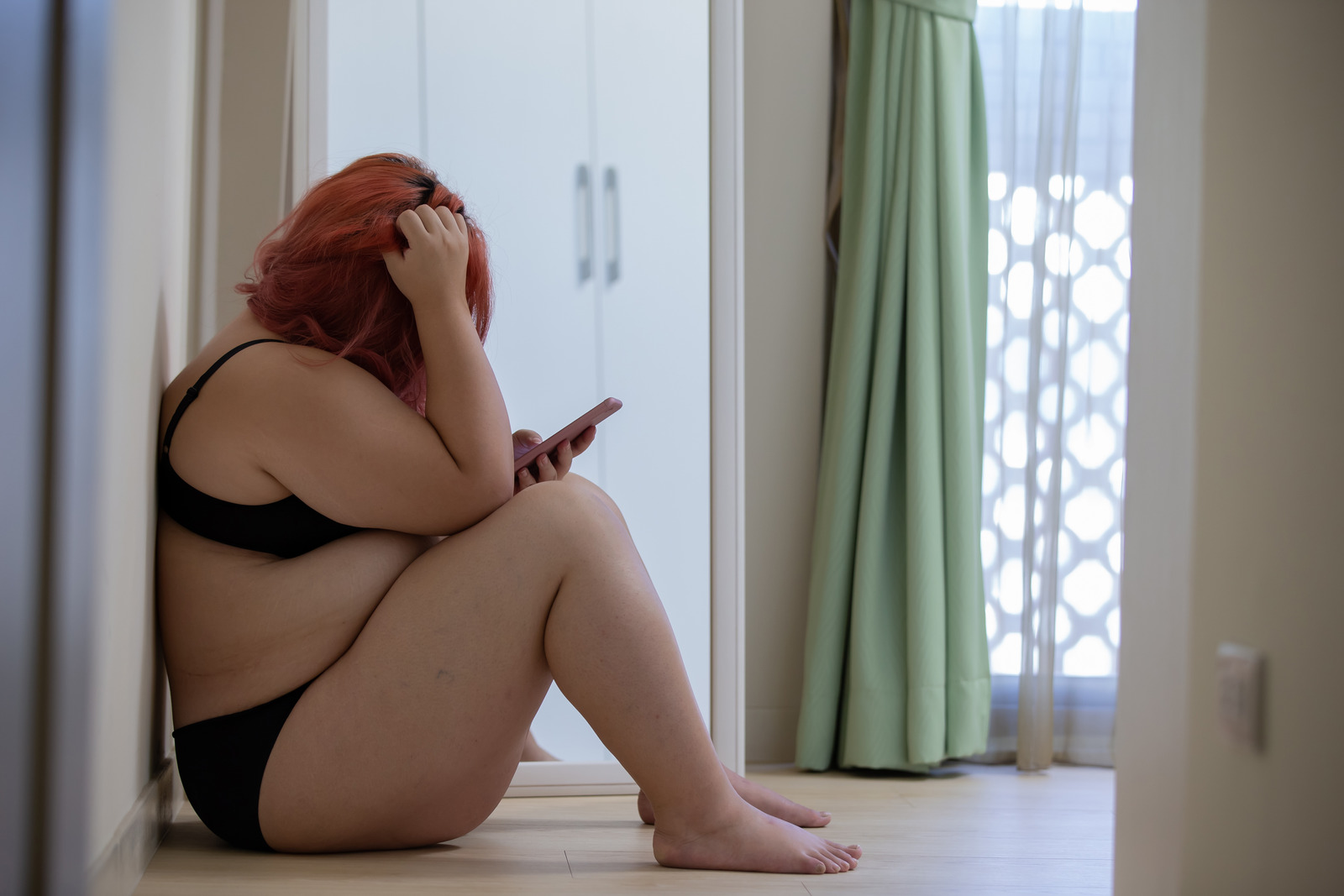 plus size woman looking at her phone in underwear STOCK PHOTO
