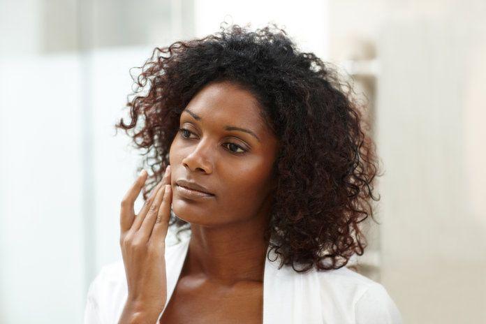Black woman applying skincare. Transepidermal Water Loss