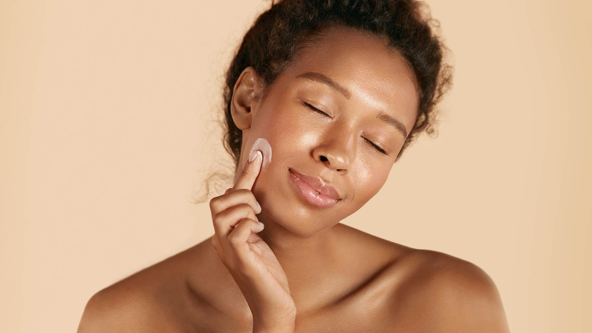Woman applying moisturizer to her face