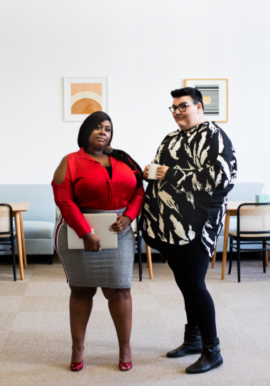 Two people stand in an office waiting room. On the left is a Black person with short cropped straight hair wearing a red v-neck long sleeve shirt with a grey skirt. Next to them stand a slightly taller white person with black hair wearing an oversized black and white designed long-sleeve shirt over black skinny jeans.