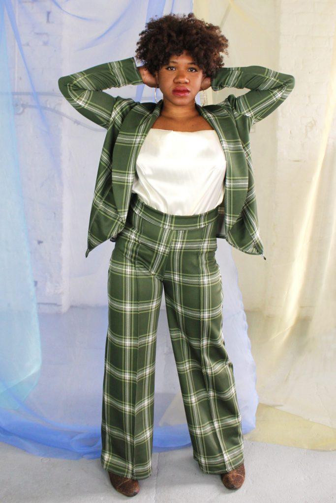 A Black person stands with their arms bent towards their head. Their hair is curly and frames their face. They are wearing a two-piece green plaid suit with a white satin blouse. they are standing in front of a light colored background.