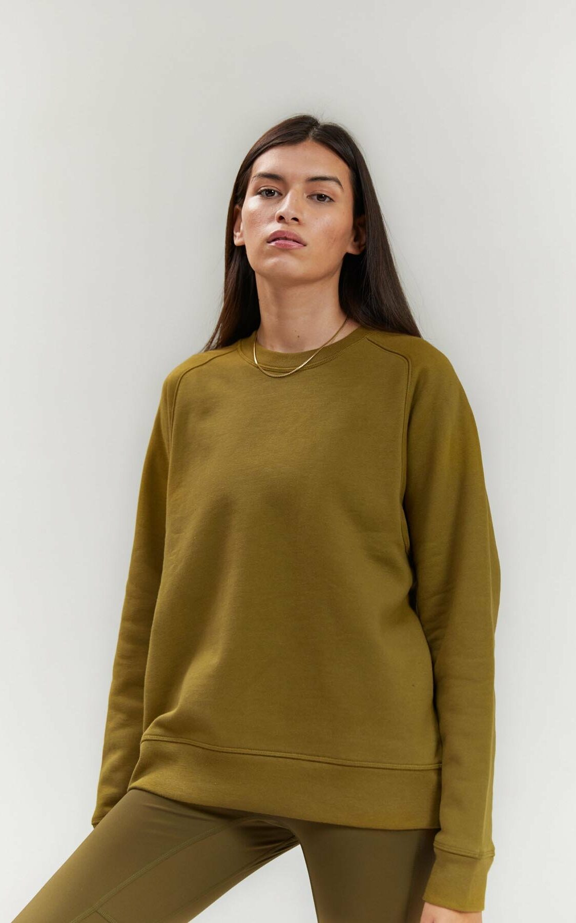 A white person with long straight brown hair stands in an olive colored crewneck.-What does Androgyny in Plus Size Fashion Mean to You? Part I