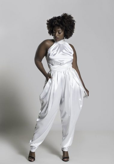 a Black person stands in an off-white satin jumpsuit with no sleeves.
