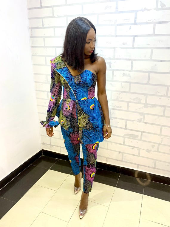 a Black person stands in a custom jumpsuit. the jumpsuit is brightly patterned in blues and pinks and has one sleeve, while the other shoulder is sleeveless. the jumpsuit has tightly cropped pants and a corset shape.