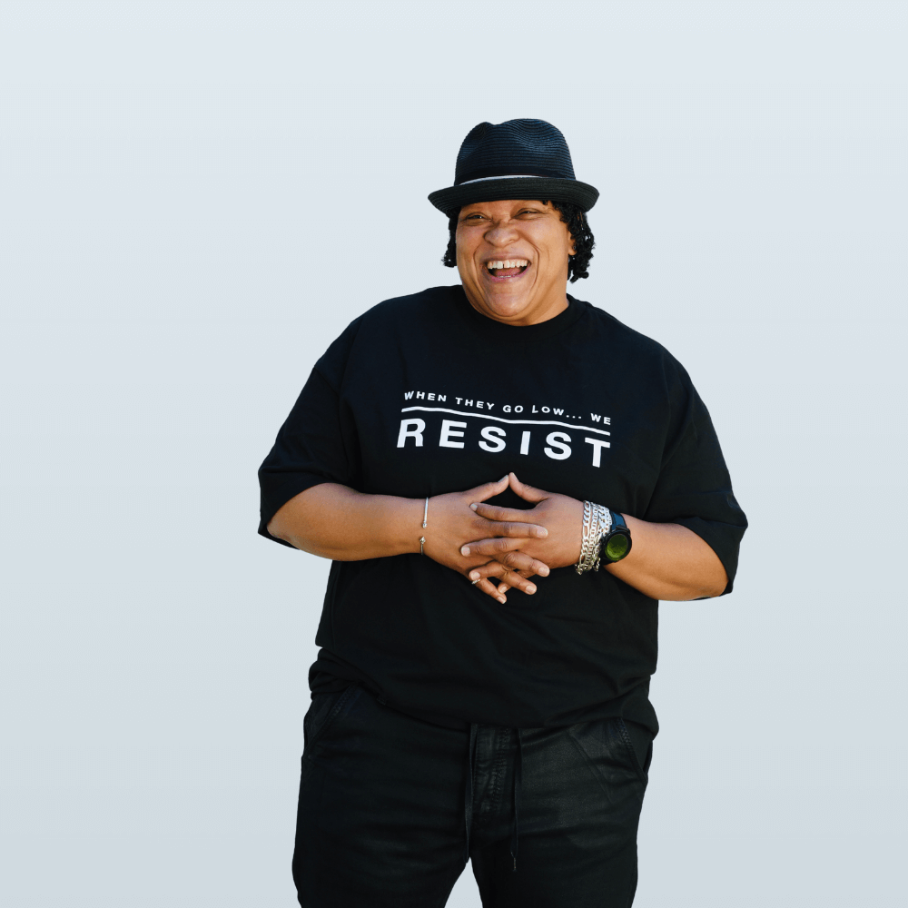"""A Black person stands with their hands folded over thei chest. Their har is short, and curly. They are wearing a black fedora and laughing into the camera. They are wearing a short sleeved androgynous black t-shirt that reads """"When they go low...we resist"""" by the Brand Haute Butch, a clothing line dedicated to Androgyny"""