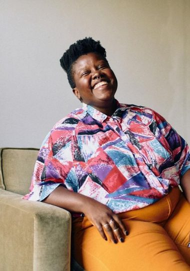 Lydia Okello sits on a chair, in orange pants and a colorful button up top, they are smiling