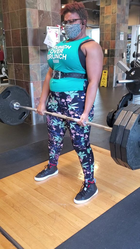 Carol wearing a Panache Sport Bra while lifting a barbell in a gym setting