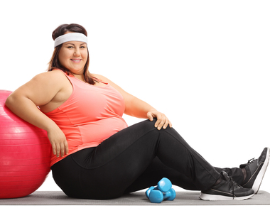 image of a plus size woman leaning on an exercise ball with weights