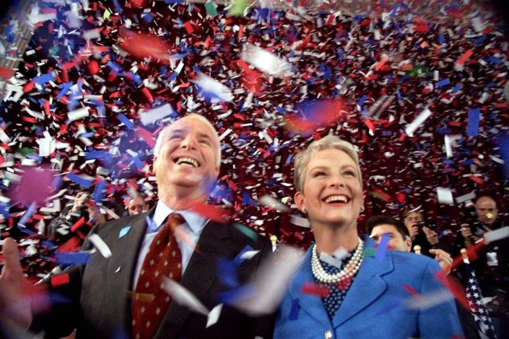 On Jan. 30, 2000, then-Republican presidential candidate Sen. John McCain, R-Ariz., and his wife Cindy, smile as confetti falls on them at the end of their 114th New Hampshire town hall meeting with voters at the Peterborough Town House in Peterborough, N.H. Peterborough was the sight of McCain's first town hall meeting in April 1999.  (Stephan Savoia/AP)