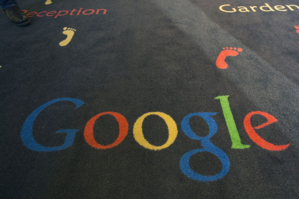 """This Tuesday, Dec. 10, 2013 file photo shows the Google logo printed on a carpet during the inauguration of the new Google cultural institute in Paris, France. French police have raided Google's Paris offices as part of an investigation into """"aggravated tax fraud"""" and money laundering, authorities said. (AP Photo/Jacques Brinon, File)"""