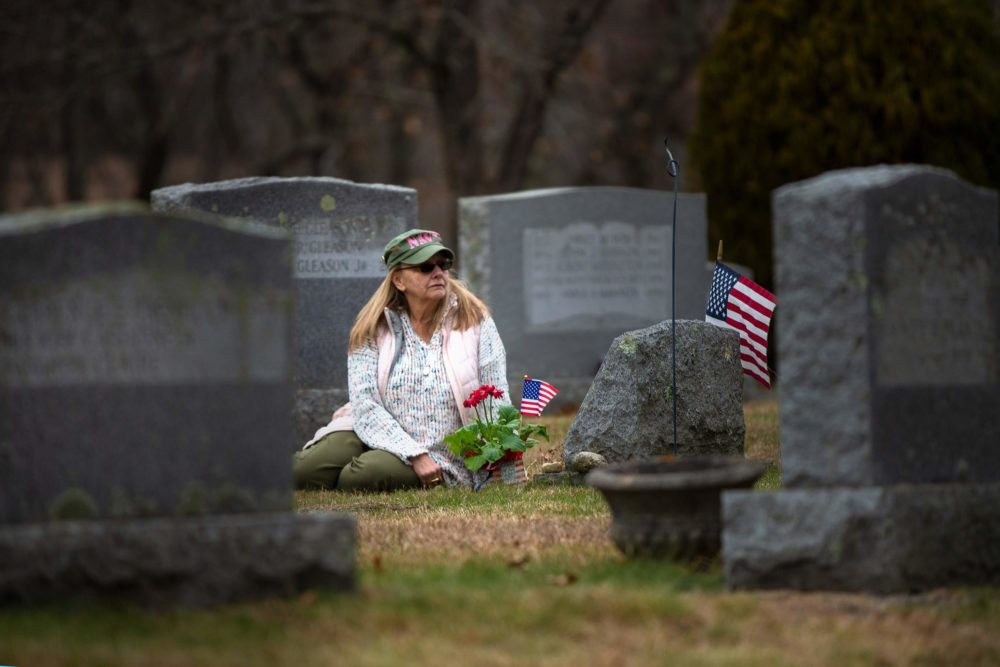 Susan Chamberlain visits the grave of her late husband, Kevin Chamberlain, at St. Augustine Cemetery in Andover. (Jesse Costa/WBUR)