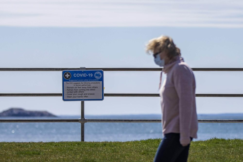 A signs hang at Kings Beach in Swampscott listing the CDC recommendations for social gathering during the Covid-19 pandemic. (Jesse Costa/WBUR)