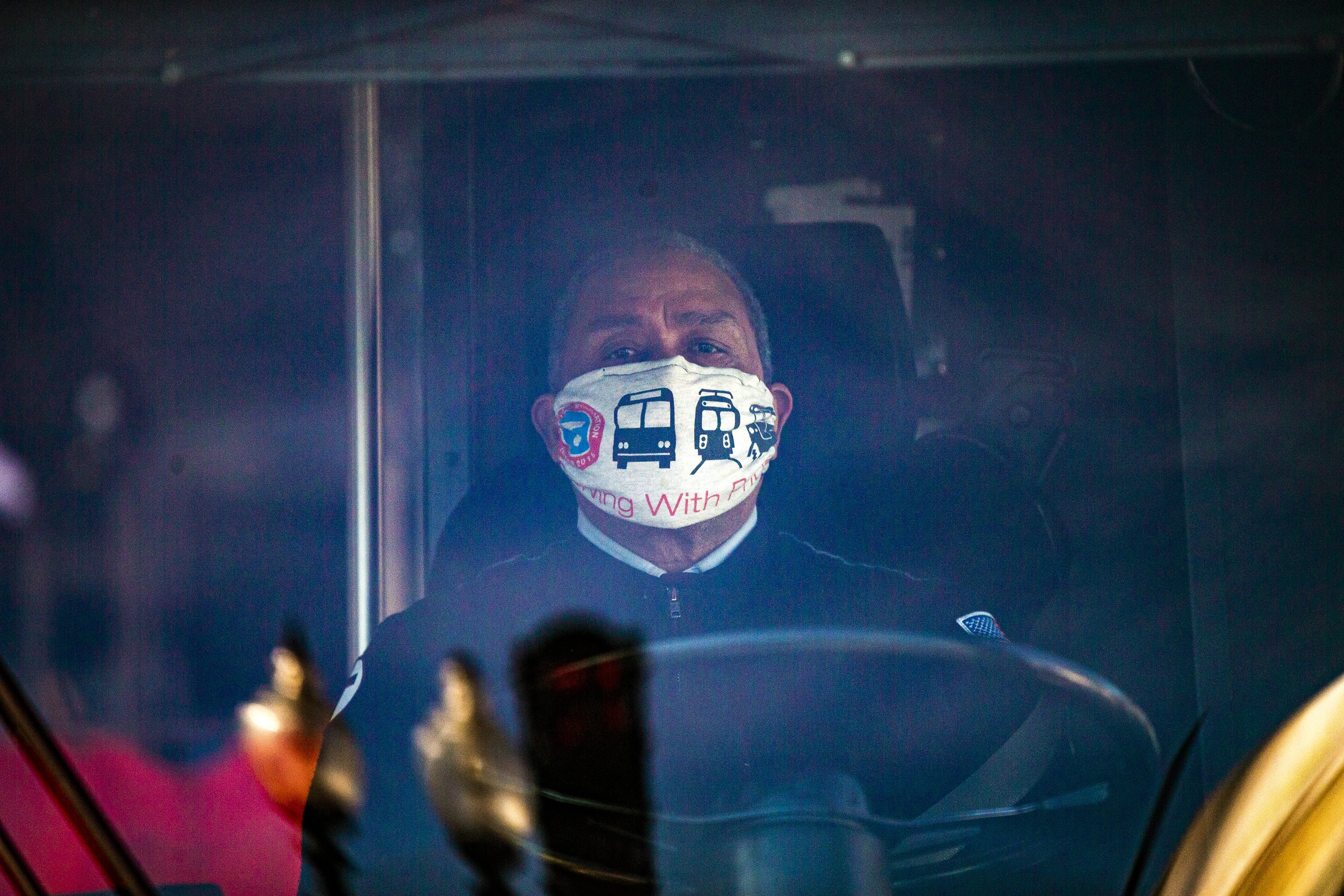 """An MBTA bus driver stopped at a traffic light on Blue Hill Ave. wearing a face mask that reads,""""Driving With Pride."""" (Jesse Costa/WBUR)"""