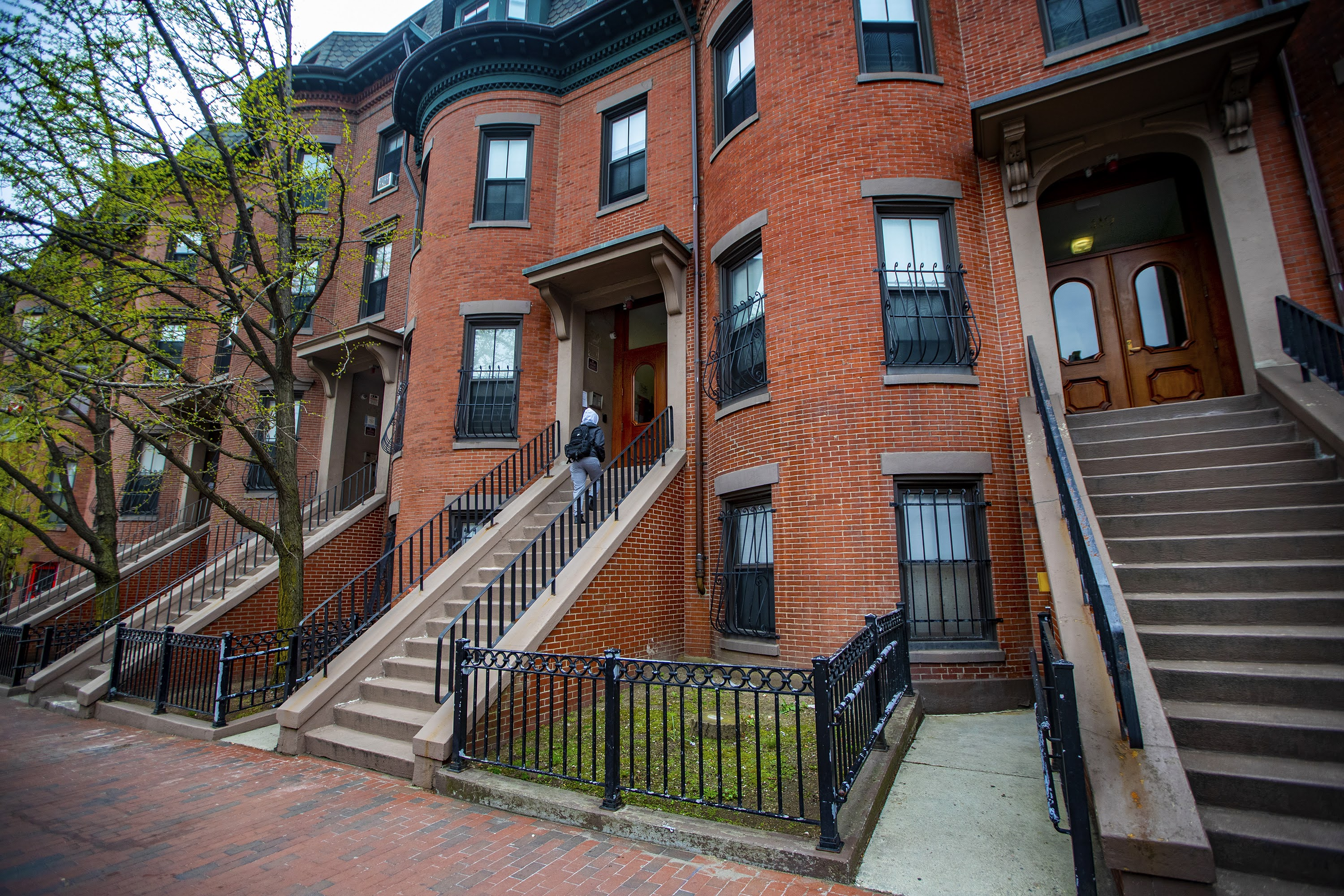 A resident of 421 Massachusetts Avenue walks up the stairs to enter her apartment, one of the building owned by the Tenants Development Corporation (TDC). All four buildings shown here, 419 - 425 Massachusetts Avenue, are owned and operated by TDC. (Jesse Costa/WBUR)
