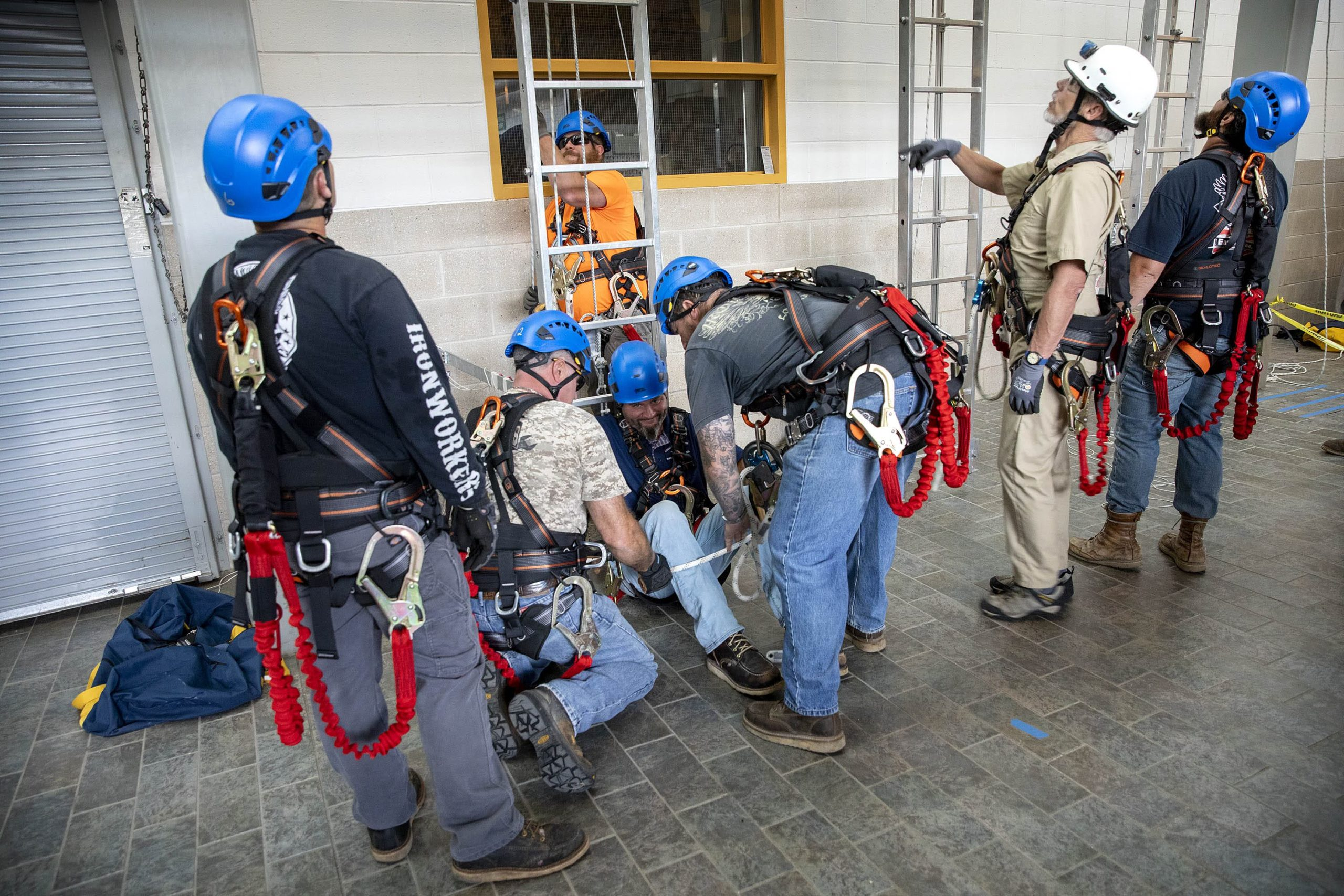 Ironworkers practice lowering an injured colleague to the ground. (Robin Lubbock/WBUR)