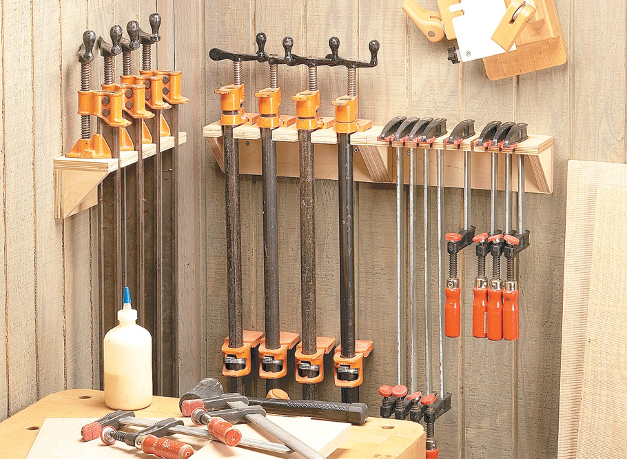 Have some scrap plywood and an empty bit of wall space? That's all you need to get your clamps organized.