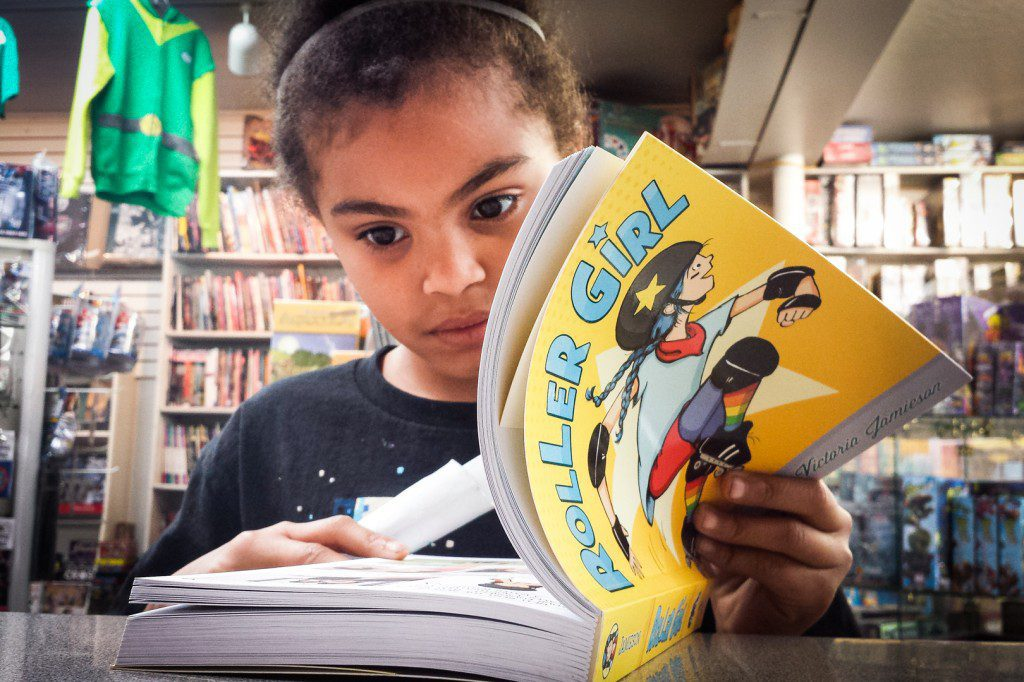 Eight year-old Nataliah Cornejo-Ayers reads a comic book at Dr. Comics & Mr. Games in Oakland, California. Photo: Olivia Cueva/Youth Radio.
