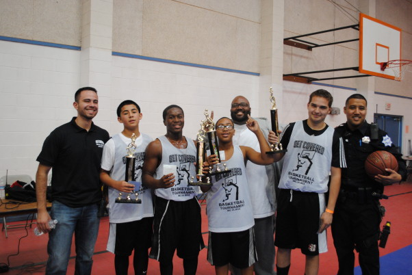 Above: Office Mike Martin, far right, poses with the winning team of young people after a community basketball tournament.  Photo by:  Mike Martin.