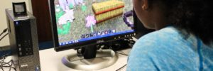 At ten years old, Maya Simon has dreams of becoming a veterinarian so today she uses Minecraft to build a farm.  Photo by: Olivia Cueva/Youth Radio