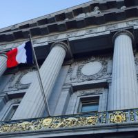A French flag billows from San Francisco City Hall in solidarity with Paris.