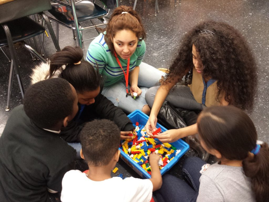 Emmie Lopez (center, top) mentors younger participants in her community during a STEM robotics activity run by the New York Academy of Sciences. (Photo credit: NYAS.)
