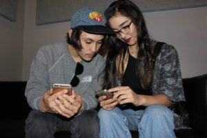 Billy Cruz and Caitlyn Clark compare social media feeds on their phones. (Photo credit Shawn Wen/Youth Radio)