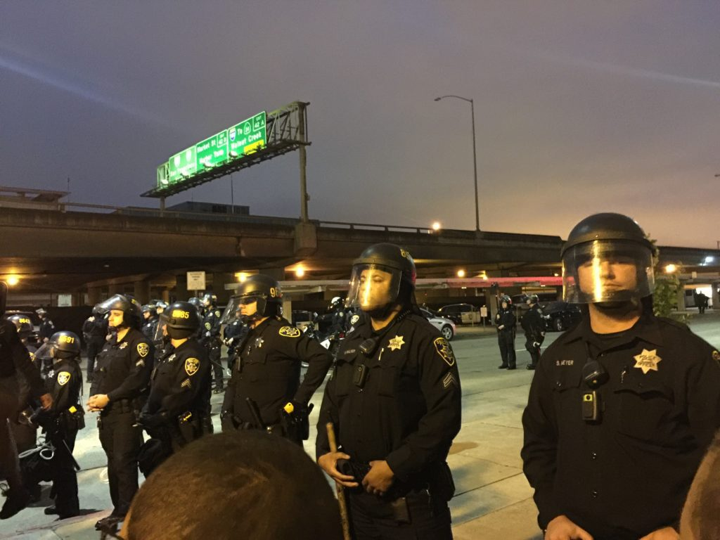 Police officers form a line near protesters in Oakland, California. Oakland was one of several cities across the country where protesters marched to protest the recent deaths of Alton Sterling (Louisiana) and Philando Castile (Minnesota), two black men who were killed by police officers. Photo: Amanda Agustin/Youth Radio