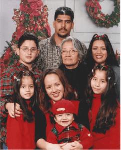 Emiliano Villa and his family poses for a portrait around Christmas, 1999. Counterclockwise from left: Dalia Pena, Jose Luis Pena, Rafael Villa, Guadalupe Valois, Gabriela Solorzano, Jazmin Pena, Emiliano Villa, and Azucena Rasilla. (Photo courtesy of Villa Family.)