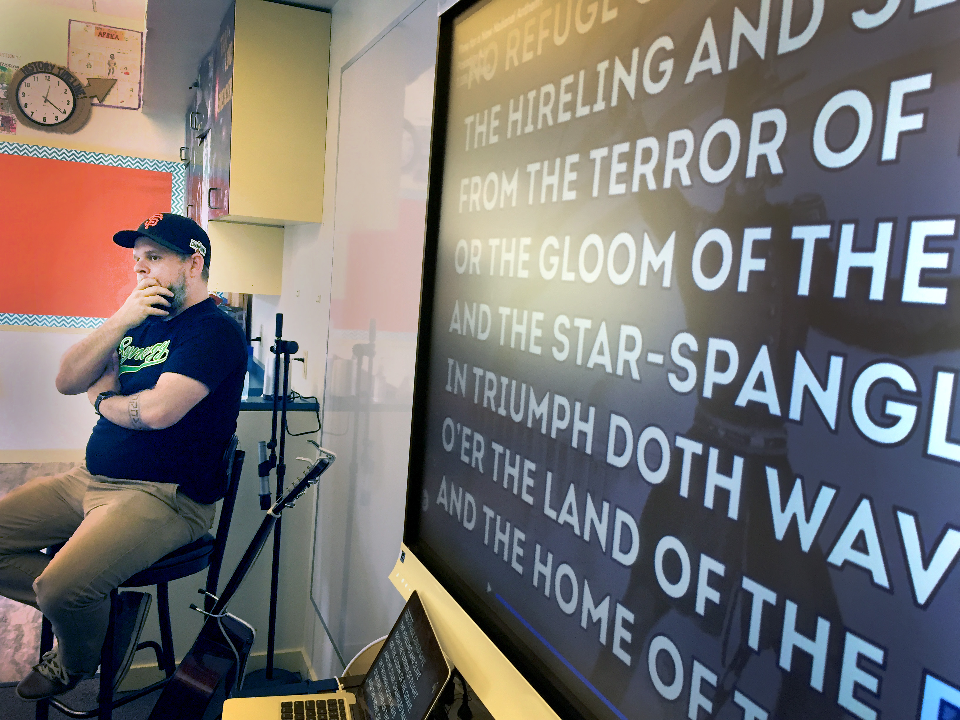 Eighth grade history teacher Dominic Altieri listens along with his students to the unsung third verse of the U.S. national antehm, which references slavery. Photo Credit: Teresa Chin/Youth Radio