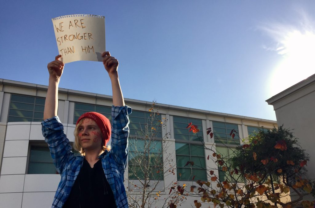 Jax Lynt, 16, holds a sign overhead at a protest at Berkeley High as helicopters circle overhead in Berkeley, California. Students marched to UC Berkeley's Sproul Plaza in reaction to Donald Trump's election to the U.S. Presidency.