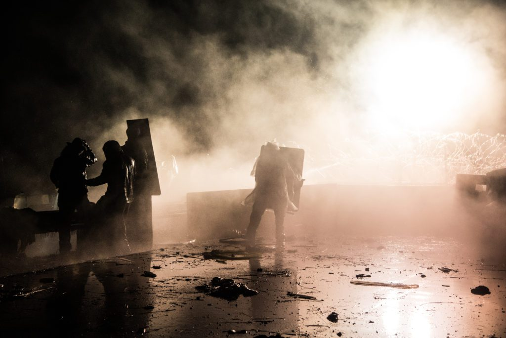 Water Defenders use makeshift shields to defend them from rubber bullets and water cannons. (Image: Avery White)