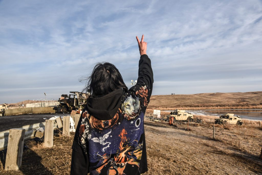 Water Defender stands with peace sign in front of a line of armed police officers and tanks. (Image: Avery White)