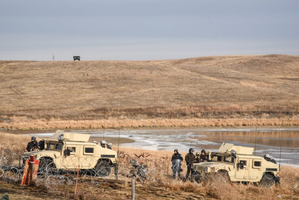 Armed Police and tanks threaten to arrest Water Defenders. (Image: Avery White)