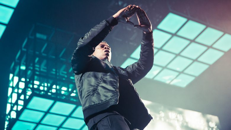 Hova makes the sign of the pyramid on stage. Oslo, 2013.